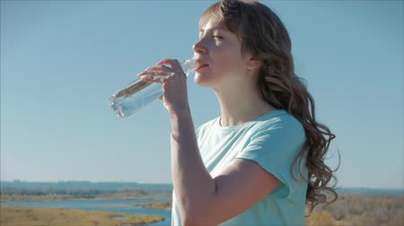 middle age : Woman of European Appearance in the Open air Drinks Water from a Bottle Against a Clear Blue Sky. Healthy Lifestyle.