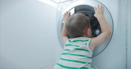prát : Cute Little Boy Looks Inside the Washing Machine. Cylinder Spinning Machine. Concept Laundry Washing Machine, Industry Laundry Service.