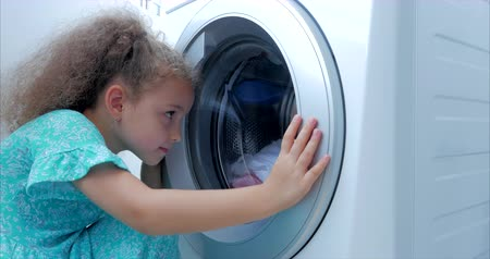 lavanderia : Cute Child Looks Inside the Washing Machine. Cylinder Spinning Machine. Concept Laundry Washing Machine, Industry Laundry Service.
