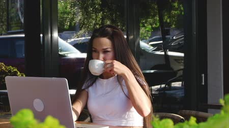 легкий : Beautiful Sunny Day Young Woman Drinks Morning Coffee in a Cafe, Making Online a Purchase Easy Payment on the Internet Using a Mobile Phone or Laptop.