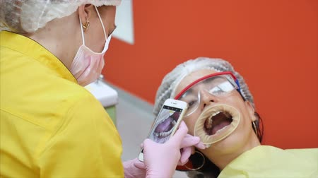 teeth brushing : Professional Dentist at Work Photographs Teeth After Treatment. A Person Undergoes a Medical Examination and Treatment of the Oral Cavity at the Dentist.