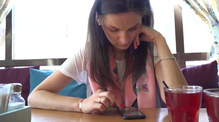 confortável : Beautiful Woman Sits in the Cafe Uses Smartphone.