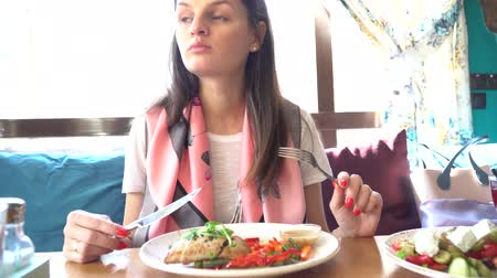 císař : Close up of salad, which is being eaten by young lady in restaurant.