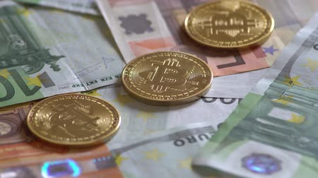 finanças : Golden Bitcoins And Euro Banknotes Rotating Stock Footage