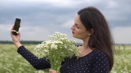 rumianek : Beautiful girl doing selfie, photo with camomile flowers outside.
