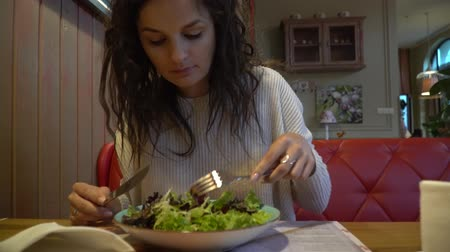 sałatka : Woman eating salad in an indoor cafe, close up on a plate.