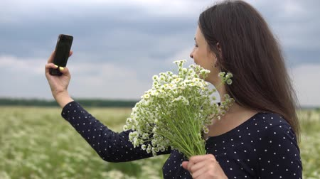 camomile : Beautiful girl doing selfie, photo with camomile flowers outside.