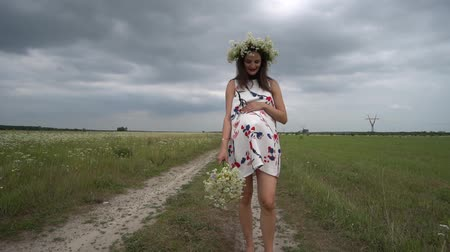 camomila : Pregnant woman with bouquet of camomile flowers.