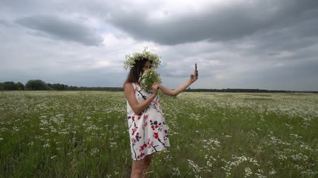 rumianek : Beautiful pregnant girl doing selfie, photo with camomile flowers outside.