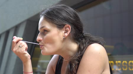 çatal : Young, attractive woman eating cake in cafe in the city cafe. Stok Video