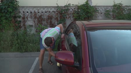 myjnia samochodowa : Young caucasian man washing his car on the car wash self-service. Car washing.
