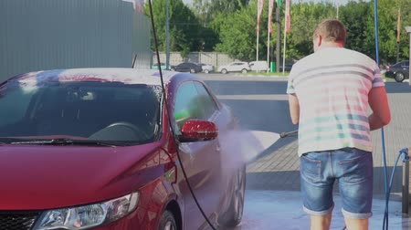 economical : Young caucasian man washing his car on the car wash self-service. Car washing.