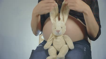 peluş : Pregnant woman playing with a bunny plush toy posing