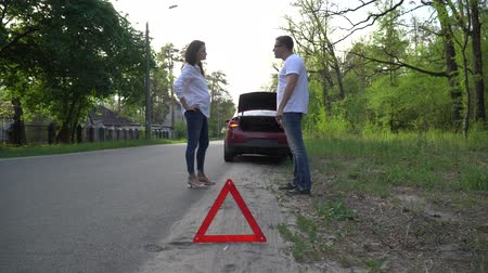 caution sign : Couple arguing in front of broken down car on quiet country road. Stock Footage