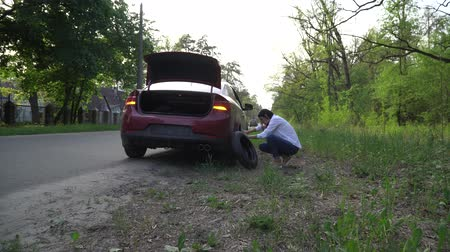 Pregnant woman changing a punctured tire at the car. repair of cars on the road. Dostupné videozáznamy
