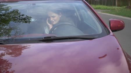 4K Woman talking on cell phone in broken down car.