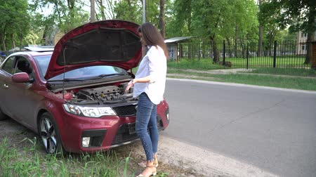 Pregnant woman and broken car calling for help on cell phone. Dostupné videozáznamy