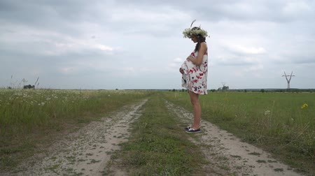 camomila : Pregnant young woman walking through chamomile field.