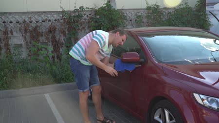 уборка : Young caucasian man washing his car on the car wash self-service. Car washing.