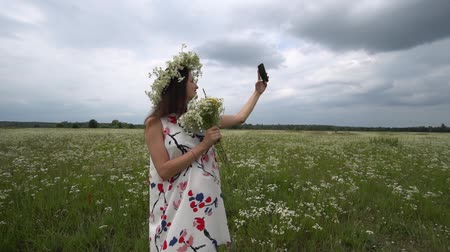 Beautiful pregnant girl doing selfie, photo with camomile flowers on the meadow Dostupné videozáznamy