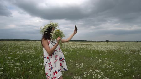 camomile : Beautiful pregnant girl doing selfie, photo with camomile flowers on the meadow Stock Footage