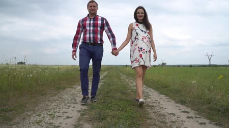 Pregnant couple walking together holding hands. Happy family concept. Woman and husband having walk outside. Man and woman holding hands. Young mother in expectation of baby. Childbearing Parenthood