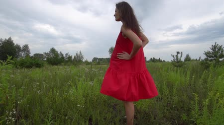 Pregnant young woman walking through the green field.
