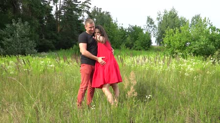 ölelés : Beautiful couple man and pregnant woman with long hair in a red dress. love, family.