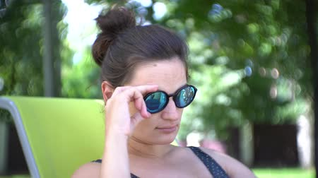 Young woman in sunglasses relaxing in the summer sun as she reclines on a comfortable deck chair.
