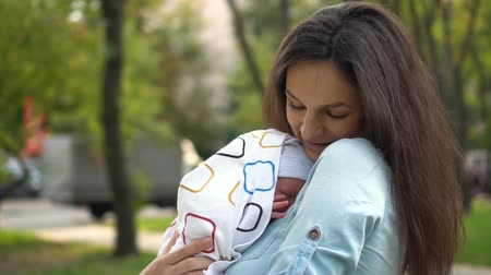 Mother and her Newborn Baby. Happy Mother holding her New born Baby girl kissing and hugging. Maternity concept. Parenthood. Motherhood. Beautiful Happy Family.