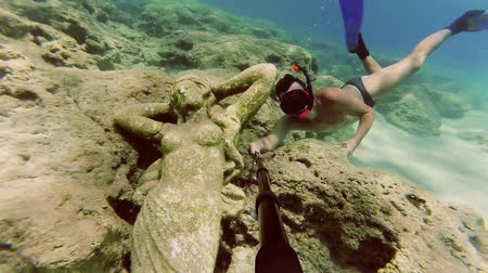 akció : Young man dives to watch statue at the bottom of the sea