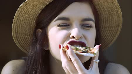 Pretty young girl at outdoor cafe eating pizza