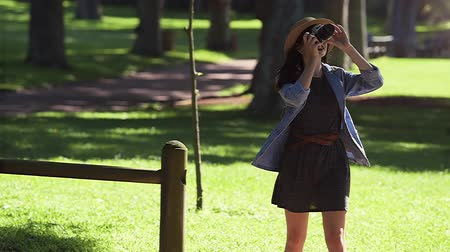 Trendy young tourist girl taking photos in a park
