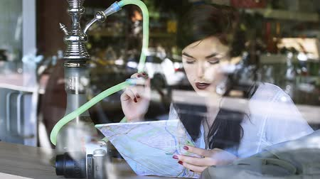 Young pretty tourist girl looking at map and smoking hookah in window