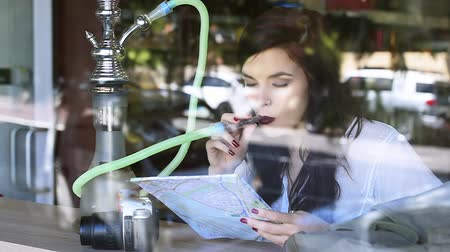 fumegante : Young pretty tourist girl looking at map and smoking hookah in window