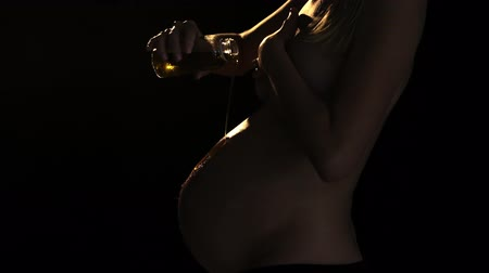 Close up as woman pours oil over her belly. Low key