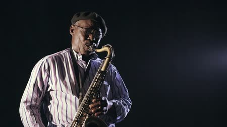 saxofone : African man colored old black playing saxophone dark background music Stock Footage