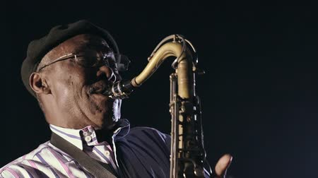 saxofone : African man colored old black playing saxophone dark background music face