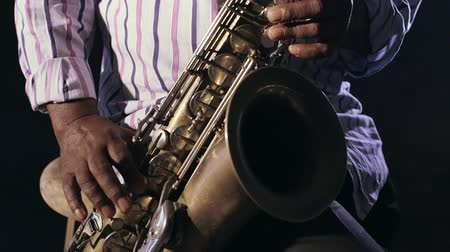 African man colored old black playing saxophone dark background music hands Стоковые видеозаписи
