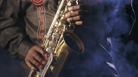 enstrümanlar : African man colored old black playing saxophone dark background music hands Stok Video