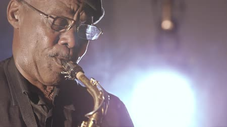 African man colored old black playing saxophone dark background music face