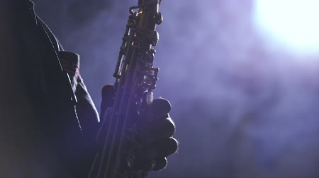 African man colored old black playing saxophone dark background music backlit silhouete face
