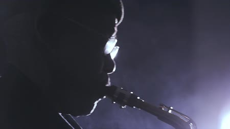 saxofone : African man colored old black playing saxophone dark background music backlit silhouete face