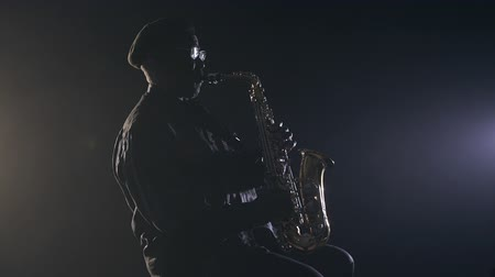enstrüman : African man colored old black playing saxophone dark background music Stok Video