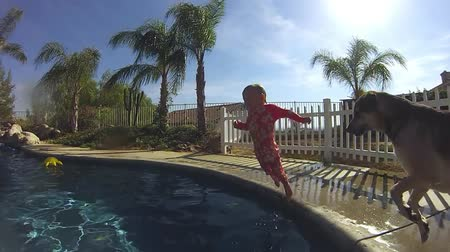 tyrkysový : Nearly 2 year old girl jumping in to the pool from the edge of the pool and swims to the nearest steps