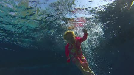tyrkysový : Underwater view little girl jumping to the pool in slow motion