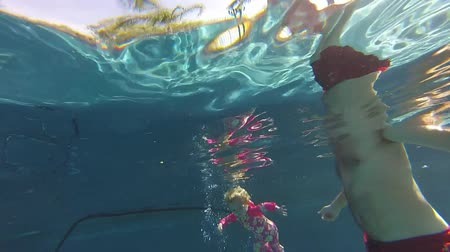 dlaždice : underwater view nearly 2 years old little girl attempts to swim long distance with her father assistance Dostupné videozáznamy