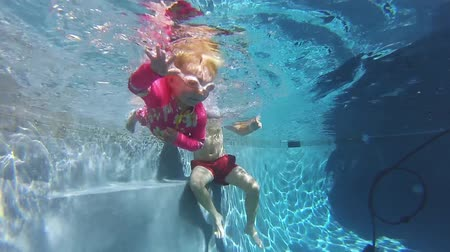 respiração : Underwater view little girl wearing goggles swims with her father assistance Vídeos