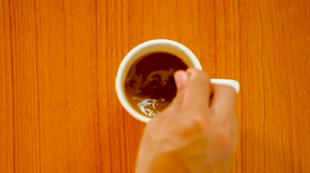 teacup : Top view of person hand stirring coffee with spoon,espresso in cup,top view beverage