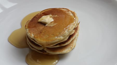 sirup : Pouring maple syrup on pancakes on a white plate